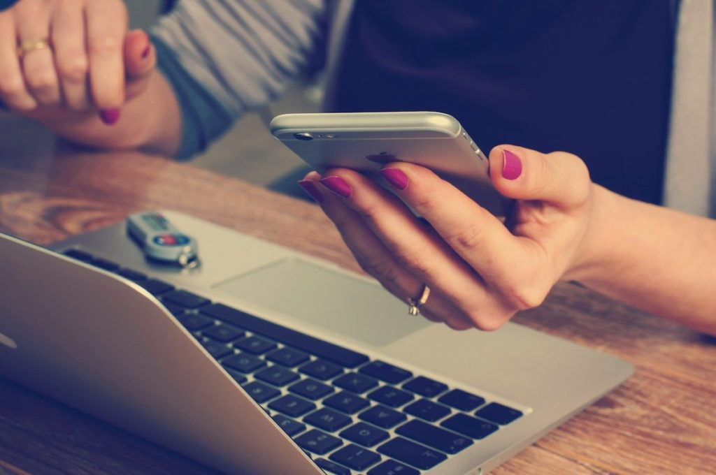 Woman using a phone and laptop
