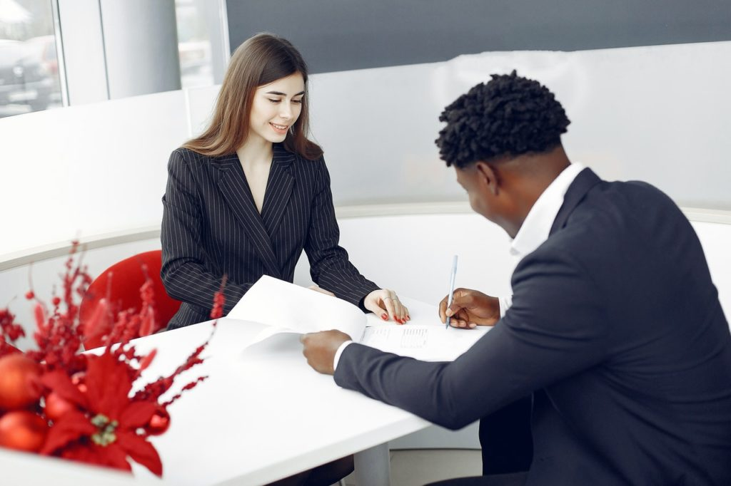 A real estate agent helps a member of the younger generation sign a contract.