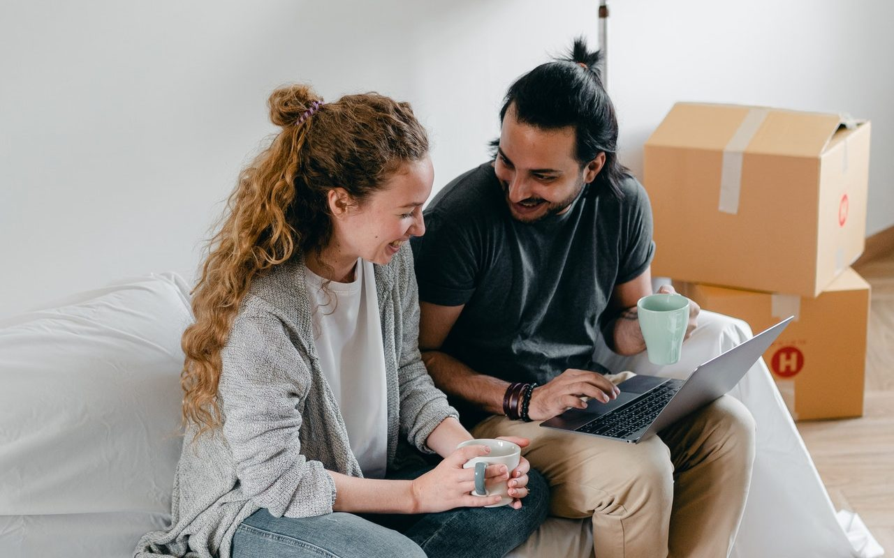 A young couple searches for a home on a laptop