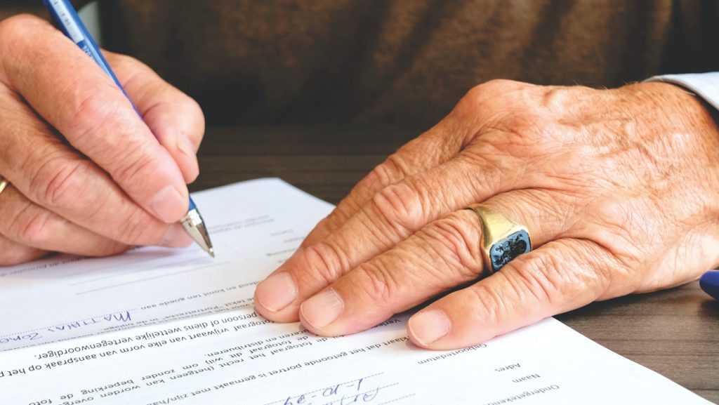 A man signs documents regarding his down payment.
